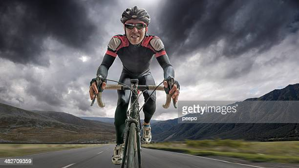 cyclist riding through storm - professional sportsperson stock pictures, royalty-free photos & images
