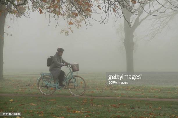 Cyclist riding through the fog in West Ham Park in Newham.