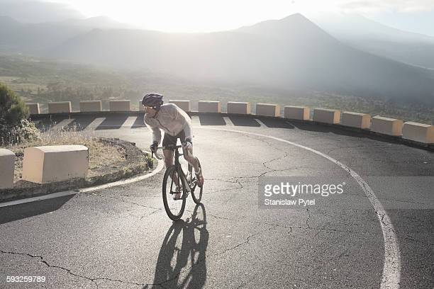 Cyclist riding up on curve in mountains