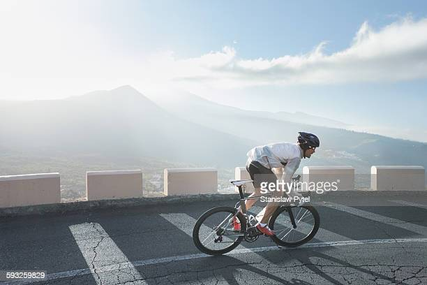 Cyclist riding up on road in mountains