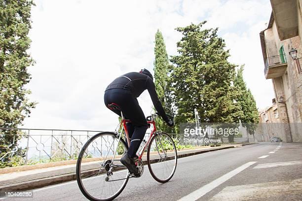 cyclist riding up road in umbria, italy - ロードバイク ストックフォトと画像