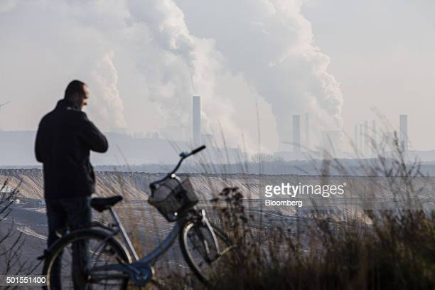 A cyclist stands beside his bicycle beside the Garzweiler open cast lignite mine operated by RWE AG in Garzweiler Germany on Tuesday Dec 15 2015...