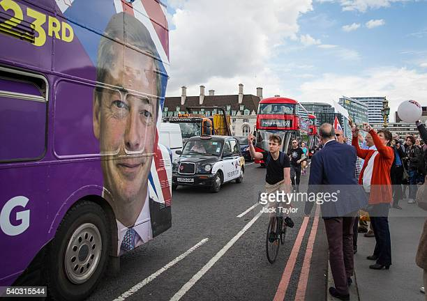 A cyclist sticks his middle finger up at a picture of UK Independence Party Leader Nigel Farage on the side of a campaign bus on Westminster Bridge...