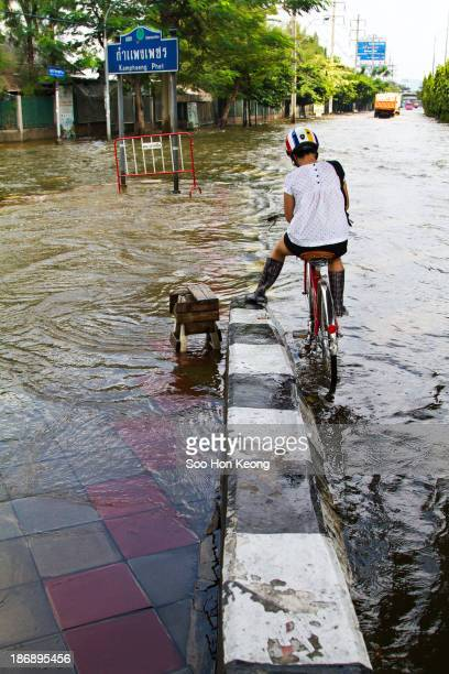 CONTENT] A cyclist stops at the intersection of Kamphaeng Phet outside of Chatuchak Weekend Market during 2011 flood