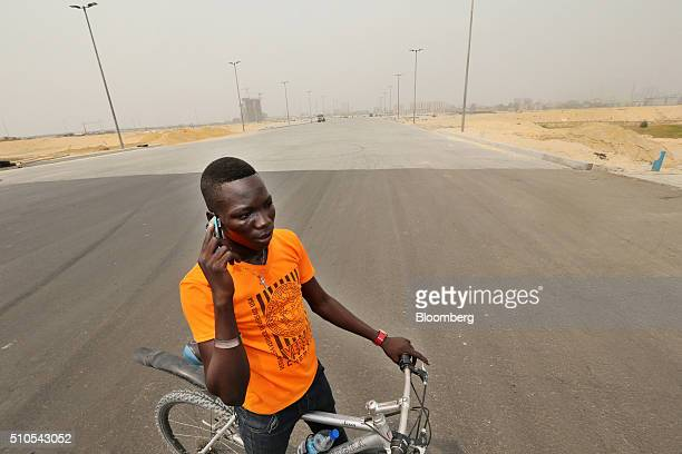 A cyclist stops to make a mobile phone call on a newly surfaced boulevard at the Eko Atlantic city site developed by Eko Atlantic near Victoria...
