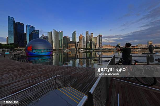 Cyclist takes a picture of the new Apple flagship store by the Marina Bay Sands waterfront on August 26, 2020 in Singapore. The store located in a...
