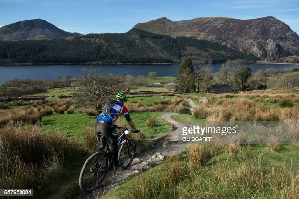 A cyclist takes part in the 'Snowdonia Mountain Bike Challenge' near Llanberis north Wales on March 26 2017 The Challenge is the only mountain bike...