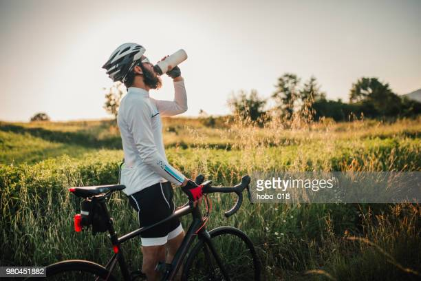 cyclist taking a rest after long ride - road cycling stock pictures, royalty-free photos & images
