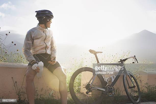 Cyclist taking break, sitting near bike