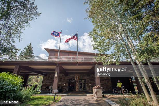 A cyclist talks on a smartphone in front of the Jackson Lake Lodge in Moran Wyoming US on Thursday Aug 23 2018 Federal Reserve Chairman Jerome...