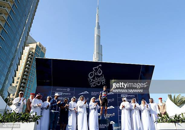 US cyclist Taylor Phinney of BMC Racing Team celebrates on the podium near United Arab Emirates officials in front of the Burj Khalifa the world's...