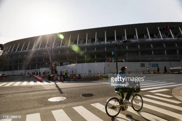 A cyclist travels past the construction site of the New National Stadium the main venue for the Tokyo 2020 Olympic and Paralympic Games in Tokyo...