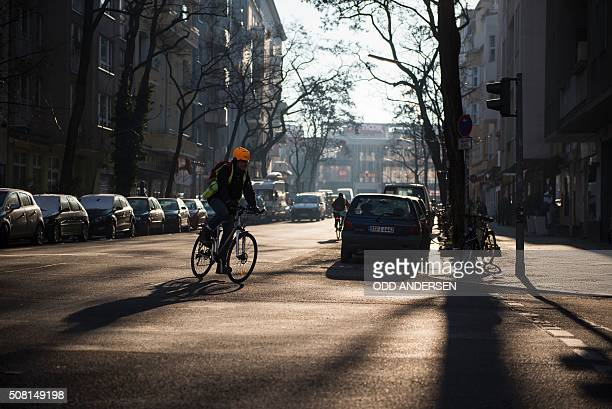 A cyclist turns into Belzigerstrasse from Akazienstrasse as the winter sun cuts through the trees casting a shadow in Berlin's Schoeneberg district...