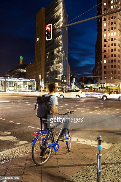 A cyclist waiting at red traffic lights at Potsdamer Platz (Berlin) - City life at rush hour in the german capital
