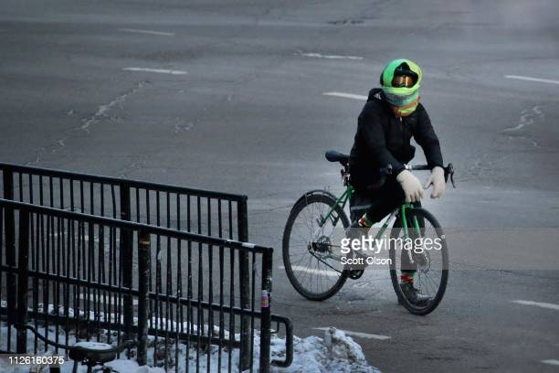 A cyclist waits in subzero temperatures for a traffic light to change on January 30 2019 in Chicago Illinois Businesses and schools have closed...