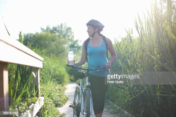 Cyclist walking bike on path through tall grass