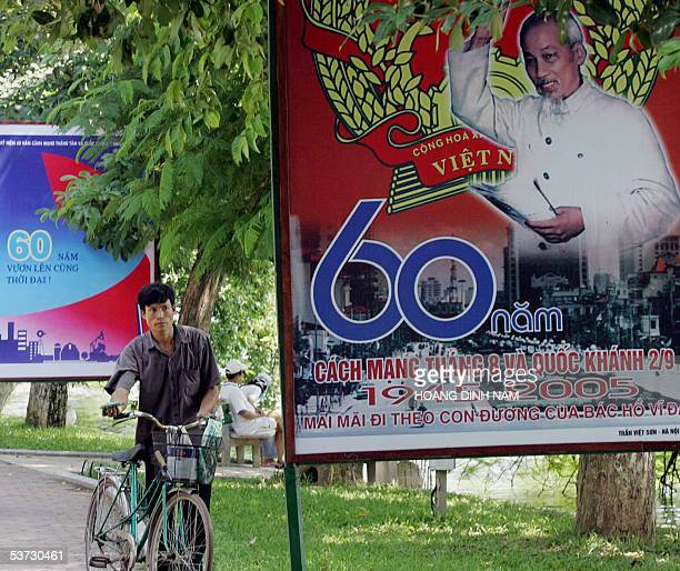 A cyclist walks past a poster showing portrait of the late Ho Chi Minh founder of modern Vietnam displayed along a park in Hanoi 01 September 2005...