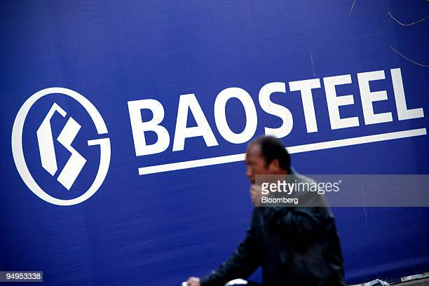 A cyclist walks past a sign outside the Baosteel Group Corp building under construction in Beijing China on Tuesday March 24 2009 Baoshan Iron Steel...