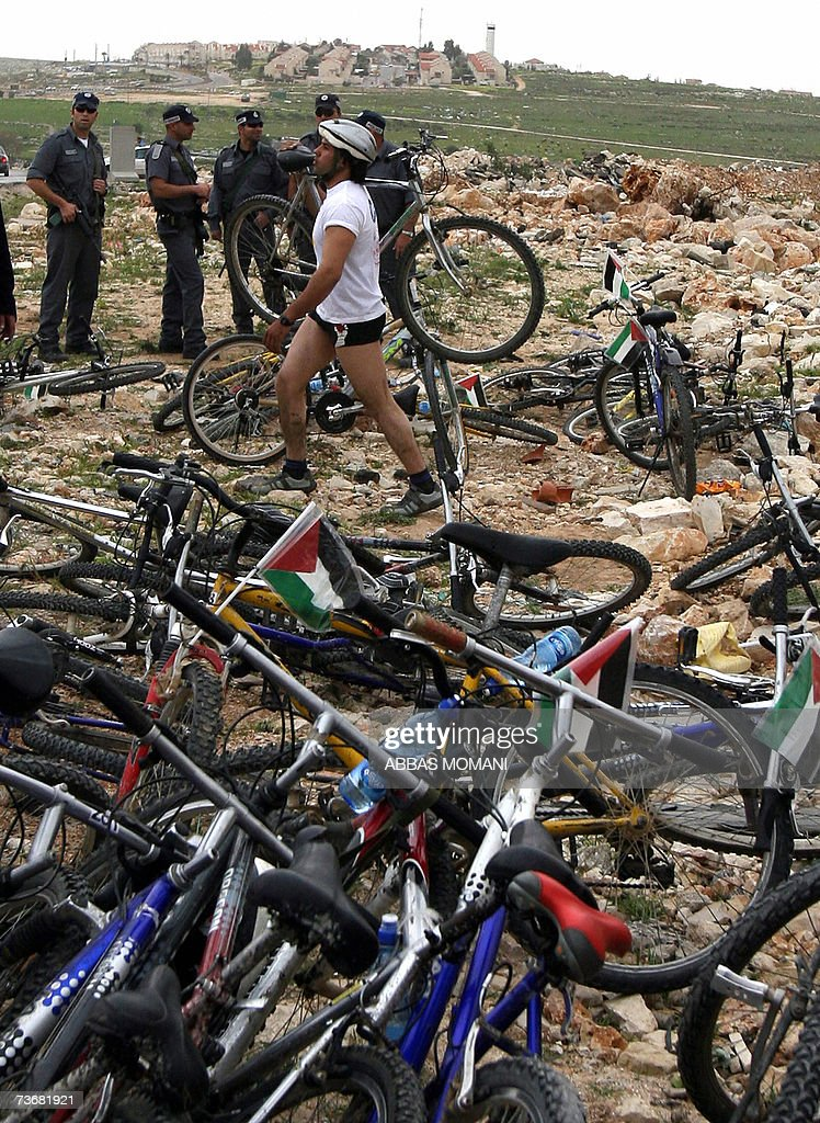 A cyclist walks past bicycles after Israeli security stopped the Palestine International Bike Race at the Jabaa Israeli manned checkpoint between the West Bank city of Ramallah and Jericho, 23 March 2007. The race was organized to protest against human rights violations, Israeli checkpoints set up through out the Israeli occupied Palestinian West Bank and restrictions on freedom of movement for the Palestinians by Israel. The race was supposed to start in Ramallah and end in the near by town of Jericho, but the cyclists were stopped by the Israeli army from reaching Jericho at Jabaa.