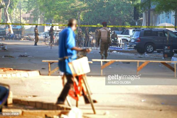 TOPSHOT A cyclist watches military personnel outside the headquarters of the country's defence forces in Ouagadougou on March 3 2018 a day after...