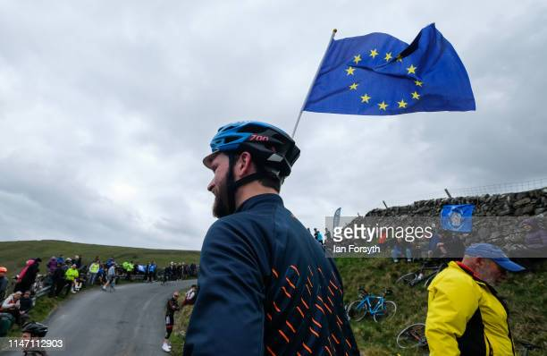 A cyclist wearing a European Union flag in his helmet waits for the arrival of the riders on the Cote de Park Rash ascent near the village of...