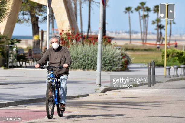 A cyclist wearing a face mask as a precaution against covid 19 riding along the beach in Vendrell Spain lifts some of the state of alarm restrictions...