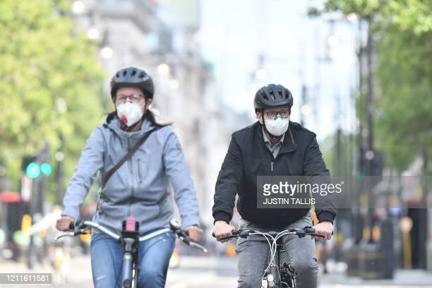 Cyclist wearing a face mask as a precaution rides along Oxford Street in London on May 2 as life in Britain continues during the nationwide lockdown...