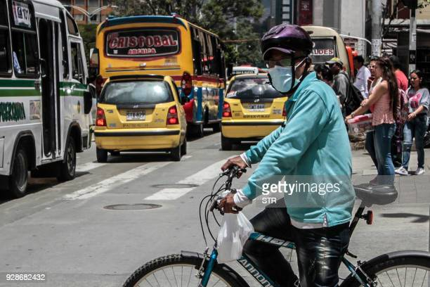 TOPSHOT A cyclist wearing a face mask in an attempt to protect himself from air pollution waits to cross a street in Medellin northwest Colombia on...