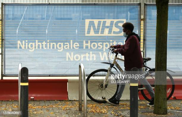 Cyclist wearing a face mask or covering due to the COVID-19 pandemic, pushes a bike past a barrier outside the NHS Nightingale Hospital North West...