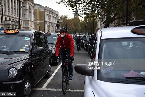 A cyclist wearing a face mask rides between taxis taking part in a protest to highlight congestion and air pollution on November 8 2016 in London...