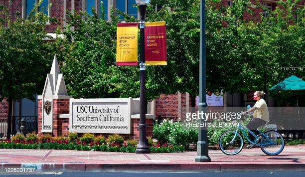 Cyclist wearing a facemask rides her bike at the University of Southern California in Los Angeles, California on August 25, 2020 where coronavirus...