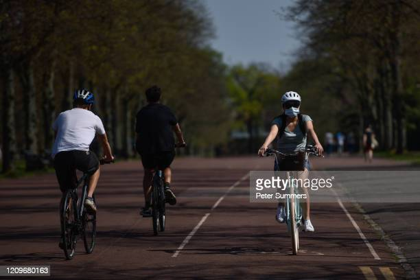 A cyclist wearing a mask is seen in Greenwich Park on April 11 2020 in London EnglandPublic Easter events have been cancelled across the country with...