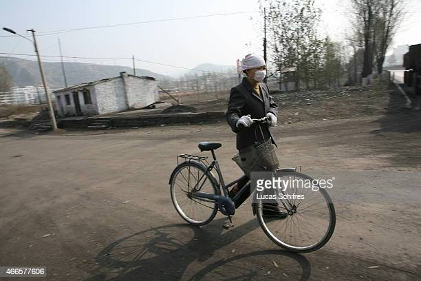 A cyclist wearing a mask pushes her bicycle in a polluted environment outside a steel factory on November 16 2007 in Zhongyang Shanxi province China...