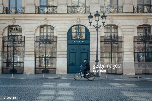 A cyclist wearing a protective face mask passes the Louis Vuitton luxury goods store operated by LVHM Moet Hennessy Louis Vuitton SE on Place Vendome...