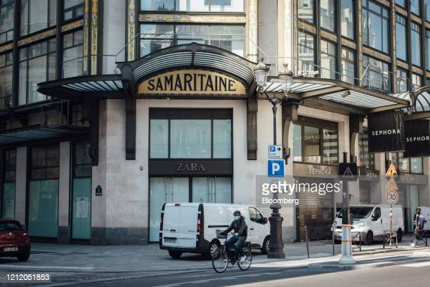 A cyclist wearing a protective face mask passes the Samaritaine luxury department store building operated by LVMH Moet Hennessy Louis Vuitton during...