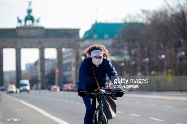 A cyclist wearing a protective mask pedals along an almost deserted 17th June street leading up to Brandenburger gate in Berlin on April 1 2020 as...