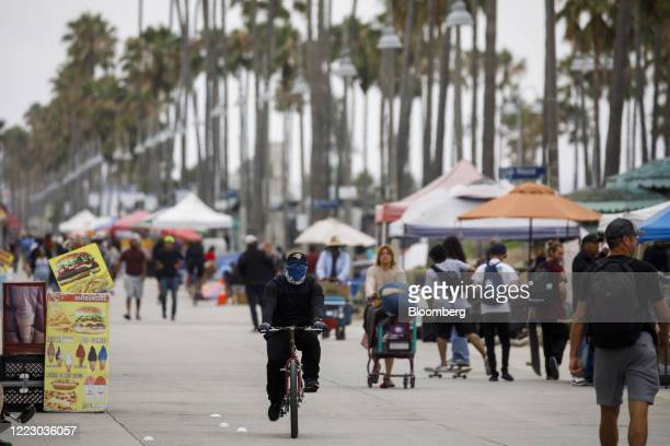 Cyclist wearing a protective mask rides at Venice Beach in Los Angeles, California, U.S., on Friday, June 26, 2020. California reported 5,349 new...