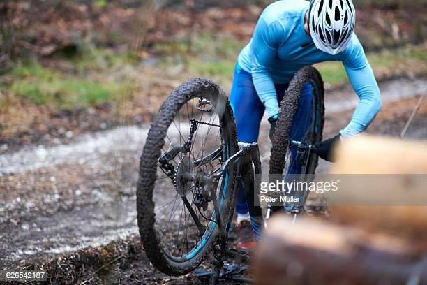 Cyclist wearing bicycle helmet repairs upside down bicycle
