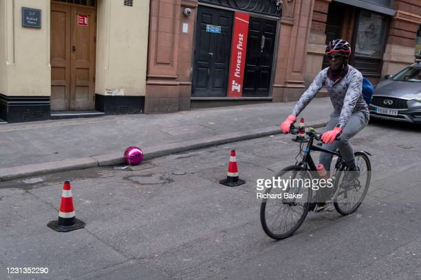 Cyclist wearing pink gloves rides past a split pink plastic sphere which has come to rest in the gutter on a side street in central London, on 23rd...