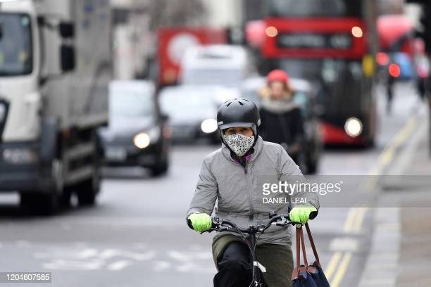 A cyclist wears a helmet and a mask as they travel by bicycle along a road in London on March 2 2020