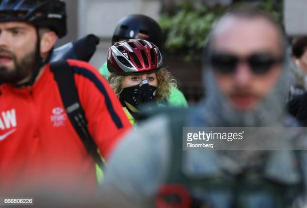 A cyclist wears a protective mask at a set of traffic lights in London UK on Monday April 10 2017 London has missed by seven years legal deadlines to...