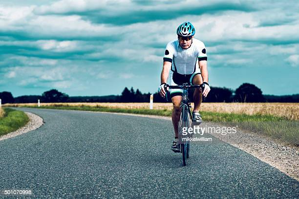 Cyclist wears helmet and rides bike on a rural road