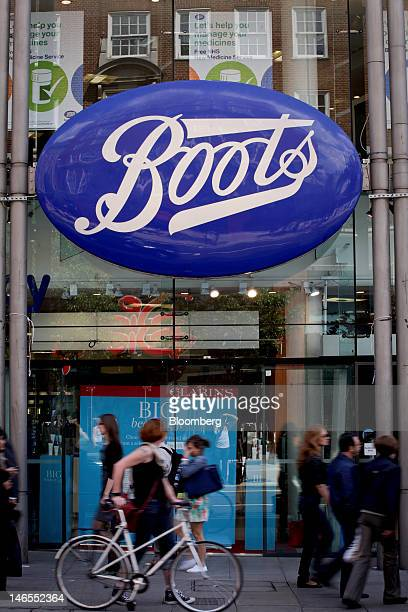 A cyclist wheels her bicycle past a Boots store operated by Alliance Boots in London UK on Tuesday June 19 2012 Walgreen Co the largest US drugstore...