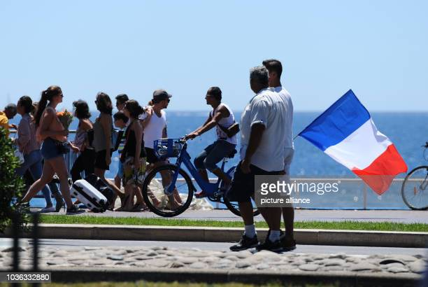 A cyclist with a French flag rides along the Promenade des Anglais near the scene where a truck drove into a crowd during Bastille Day celebrations...