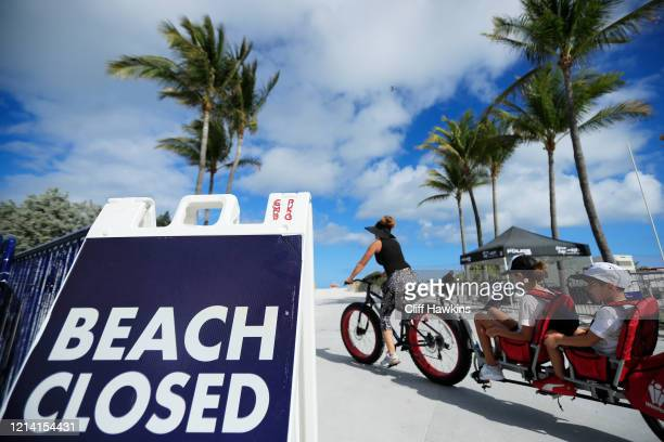 A cyclist with a trailer for children passes a Beach Closed sign on the boardwalk on March 22 2020 in Miami Beach Florida The city of Miami Beach has...