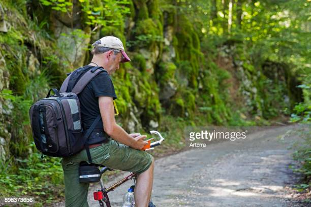 Cyclist with backpack riding a bicycle stopping to take a break for texting and reading smartphone along a forest road in summer