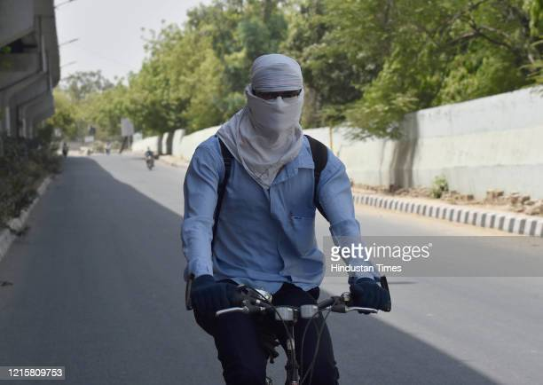 Cyclist with cloth wrapped around his head to beat the heat on a hot summer day near Rao Tula Marg, on May 27, 2020 in New Delhi, India.
