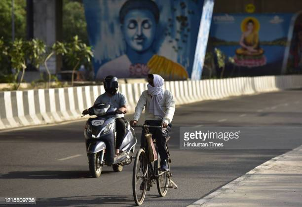 Cyclist with his head wrapped with a cloth to protect from the sun on a hot summer day at Sector 35, on May 27, 2020 in Noida, India.