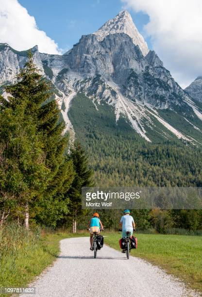 cyclist with mountain bikes, on the via claudia augusta cycle path, crossing the alps, sonnenspitze at the back, mountain landscape, near ehrwald, tyrolean alps, tyrol, austria - aktiver lebensstil stock-fotos und bilder