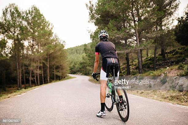 Cyclist with racing cycle on a road